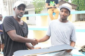 Baraka Bishota hands Abubakar Amour his prizes he won after being the Winner of Flat Ground League - Tanzania Finals